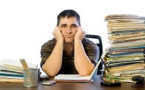 bored teacher surrounded by stacks of papers to grade