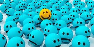 A one yellow happy face smiles among a bunch of unhappy blue faces